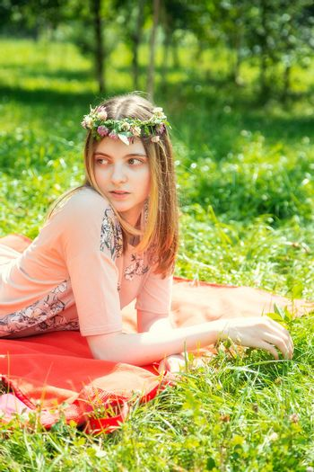 Young girl 20 years old Caucasian appearance smiling looking to the side lying on the lawn in the park on a summer day. The girl is dressed in a T-shirt and jeans and a wreath of wildflowers.