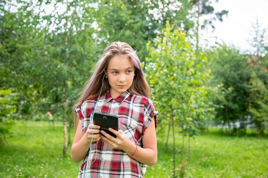A young girl of 15 years old Caucasian appearance looks around and holds a mobile phone in her hands in the park on a summer day. The girl is dressed in a plaid shirt and jeans.