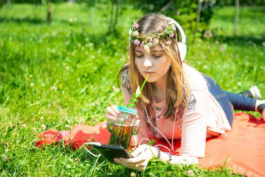 A young girl of 20 years old Caucasian appearance listens to music on her mobile phone and drinks smoothies from a large glass, sitting on the lawn in the park on a summer day.