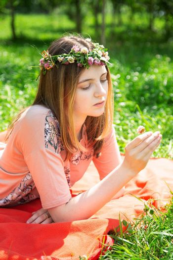 A young girl of 20 years old Caucasian appearance examines a flower lying on the lawn in the park on a summer day. The girl is dressed in a T-shirt and jeans and a wreath of wildflowers.