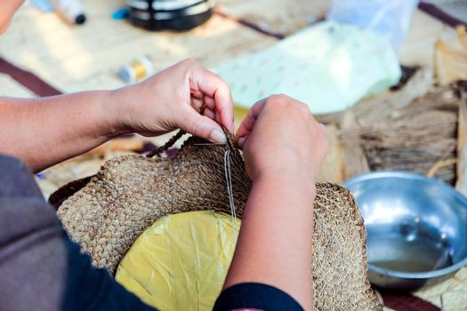 Hands of Thai female artisans is using a needle weaving sew hat that woven comes from plants