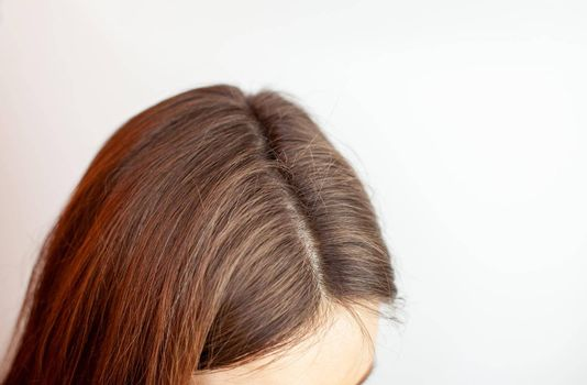 A woman's head with a parting of gray hair that has grown roots due to quarantine. Brown hair on a woman's head close-up.