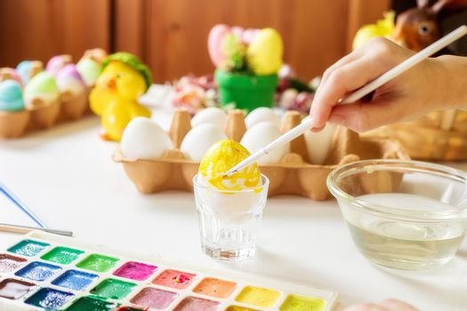 A close-up on the hands of a small Caucasian girl 5 years old paints eggs with special water paints for the Christian spring holiday of Easter. Girl dressed in a yellow floral dress