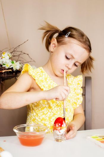A small Caucasian girl of 5 years old paints eggs with special water paints for the Christian spring holiday of Easter. The girl is dressed in a yellow floral dress and has ponytails.