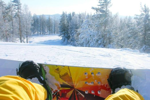 Snowboarder sitting on snow, legs snowboard and slope