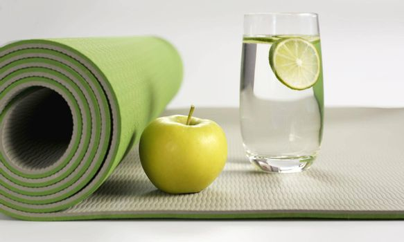 Yoga fitness, health life style. Yoga rolled green mat , green apple, glass of water with lemon on white background. Place for text. Healthy lifestyle, fitness, sport concept