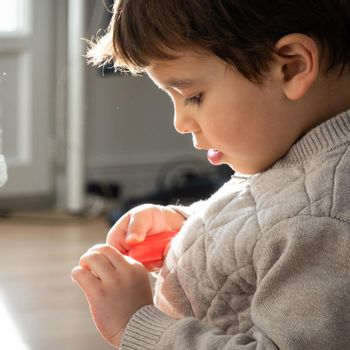 Portrait of backlit little boy playing at home