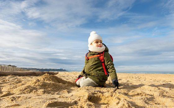 Little boy looking away on beach, beautiful winter season
