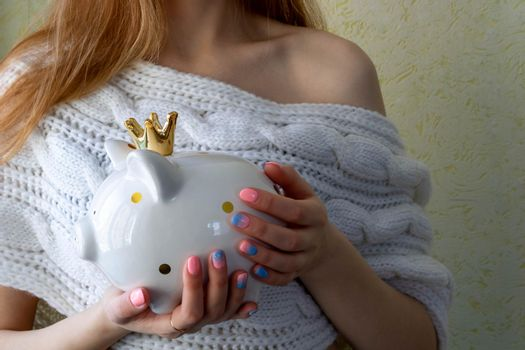 The girl's hands hold a white piggy bank with a golden crown.