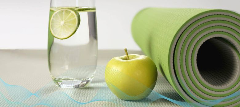 Yoga fitness, health life style. Yoga rolled mat, apple, glass of water with lemon, abstract wave. Place for text. Healthy lifestyle, fitness, sport concept