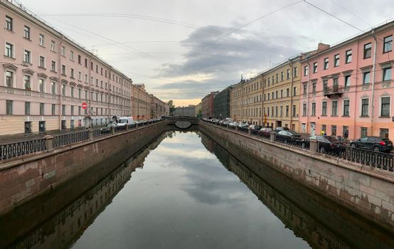 Russia, St.Petersburg, 09 June 2020: Griboyedov Canal at sunset, specular reflection in water, architecture of St. Petersburg, the bridge through the river