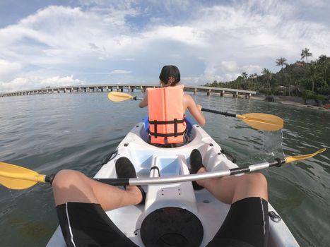 Couple traveler kayaking together on the sea  from backward view.