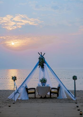 A loving couple shares a romantic dinner with candles, lanterns, and wine glasses at sea beach sand against wonderful sunset. Romantic dinner on the beach