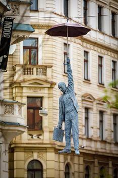 Sculpture of a Hanged Man with an Umbrella, titled Little Uncertainty by Michal Trpak in Prague Czech Republic