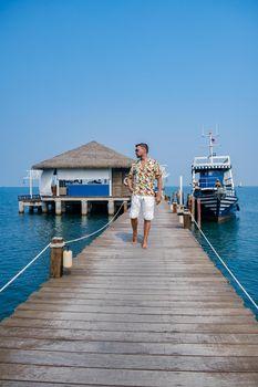wooden pier in ocean Pattaya Bangsaray beach Thailand, a man walking on wooden pier during vacation Thailand. Asia