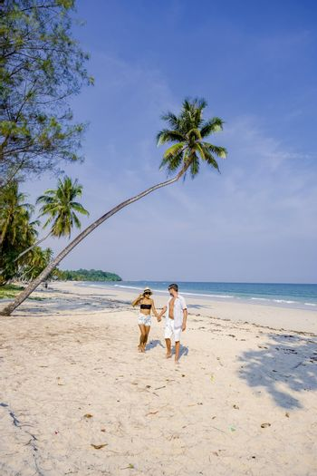 couple on vacation in Thailand, Chumpon province, white tropical beach with palm trees, Wua Laen beach Chumphon area Thailand, palm tree hanging over the beach with a couple on vacation in Thailand.