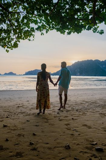 couple watching the sunset on the beach, European man and Asian woman sunset on the beach in Krabi Thailand. Asia