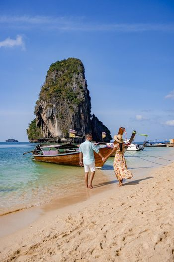 couple mid age on a tropical beach in Thailand, tourist on a white tropical beach, Railay beach with on the background longtail boat. Railay Beach in Krabi province. Ao Nang, Thailand.