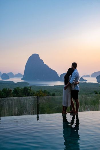 couple men and woman mid age watching sunrise in Phangnga bay Thailand, Phangan bay viewpoint, couple watching sunrise on the edge of a swimming pool, infinity pool look out over Phangnga Bay Thailand