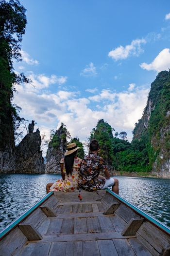 couple on longtail boat visiting Khao Sok national park in Phangnga Thailand, Khao Sok National Park with longtail boat for travelers, Cheow Lan lake, Ratchaphapha dam. man and woman mid age vacation