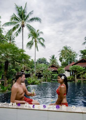 men and woman mid age in swimming pool in Asia, couple European man and Asian woman on vacation relaxing by pool