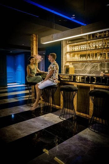 men and woman sitting by the bar drinking cocktail in a dark room with light behind the bar in a tropical country. couple mid age drinking by the bar