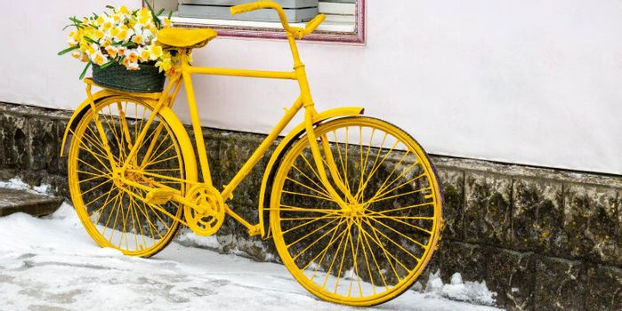 An old yellow bicycle stands against a wall in winter, in vintage style.