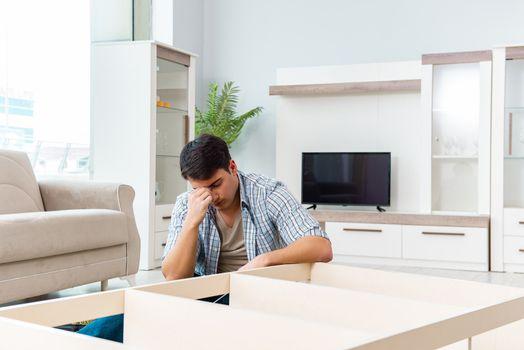 Man assembling furniture at home