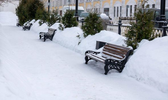 Winter landscape.Snow-covered benches in the alley.