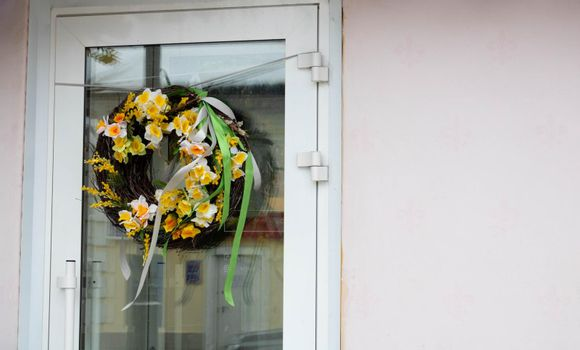 Photo of a seasonal spring wreath with daffodils on a glass door.