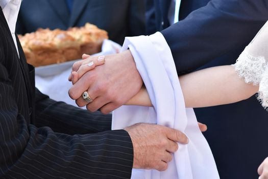 The bride and groom hold hands. The parent ties their hands together with a white towel.