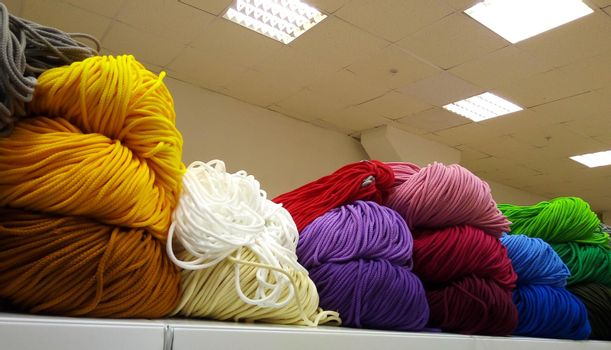 A bunch of colorful shoelaces. A bunch of colorful threads for sports shoes, lying on a shelf in the store.
