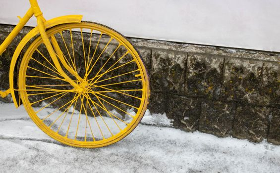 A yellow bicycle wheel stands against a wall, in vintage style.