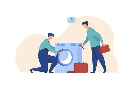 Two repairmen fixing washing machine