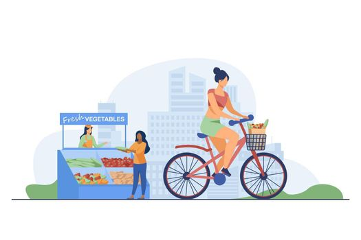 Woman cycling and buying fresh vegetables