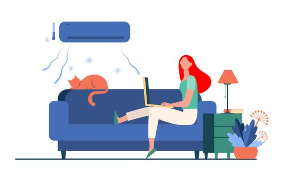 Woman sitting on sofa with cat and laptop under air conditioner