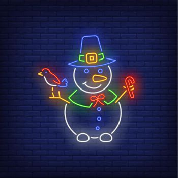 Snowman wearing witch hat, holding bird and candy cane neon sign
