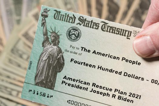 Illustration of the 2021 federal stimulus payment check from the IRS with cash