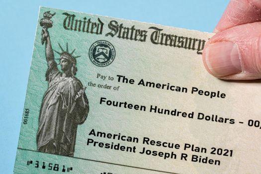 Illustration of the 2021 federal stimulus payment check from the IRS with hand