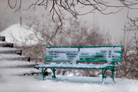 Winter Scene. Green Bench near the Stairs in the Park Covered with Snow. Wintertime Outdoors.