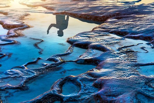 Reflection of a Tourist in the Travertine Pools in Mild Sunset Light.  Beauty of Nature. Famous Touristic Attraction. Pamukkale. Turkey.