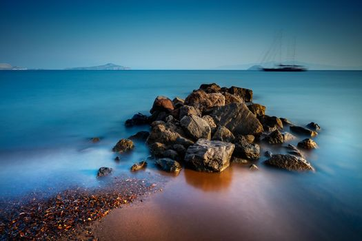 Beautiful Landscape of a Stony Heap on the Coast of Mediterranean Sea with Blurry Moving Ship on Background. Summer Feel. Greece.