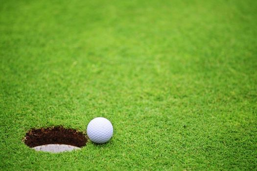 Golf ball close to hole, on lip of cup on green of golf course background with copy space for text banner