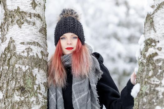 Portrait of attractive red hair girl posing between two birches