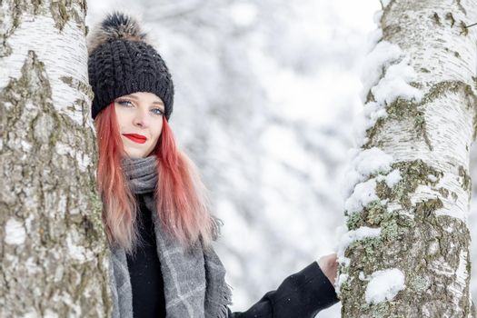 Attractive red hair girl is posing between two birches