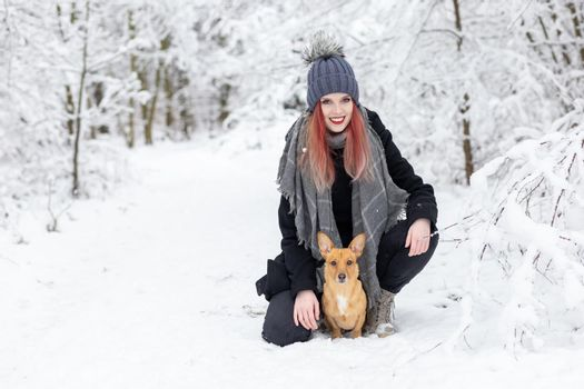 Smiling girl is posing with her brown dog in snowy path.