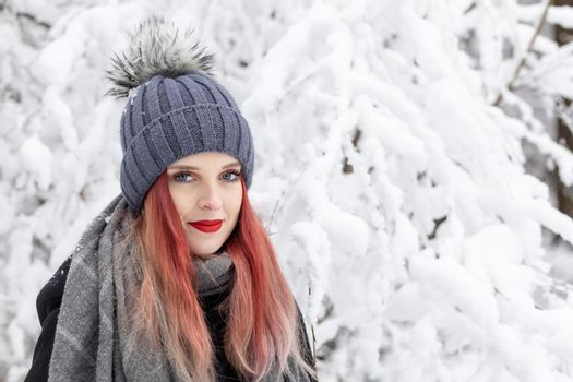 Portrait of smiling red hair and red lips girl in snowy day.