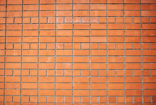 A new, smooth red brick wall. The bricks are laid in rows. Grunge stone texture. There is a place for the text