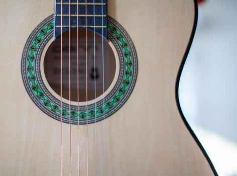 Close-up of a guitar player or a person learning to play an acoustic guitar. Home learning to play a musical instrument