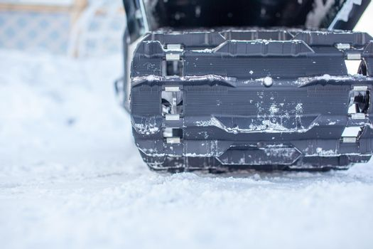 The back of a snowmobile in winter and riding in the snow on a snowmobile.